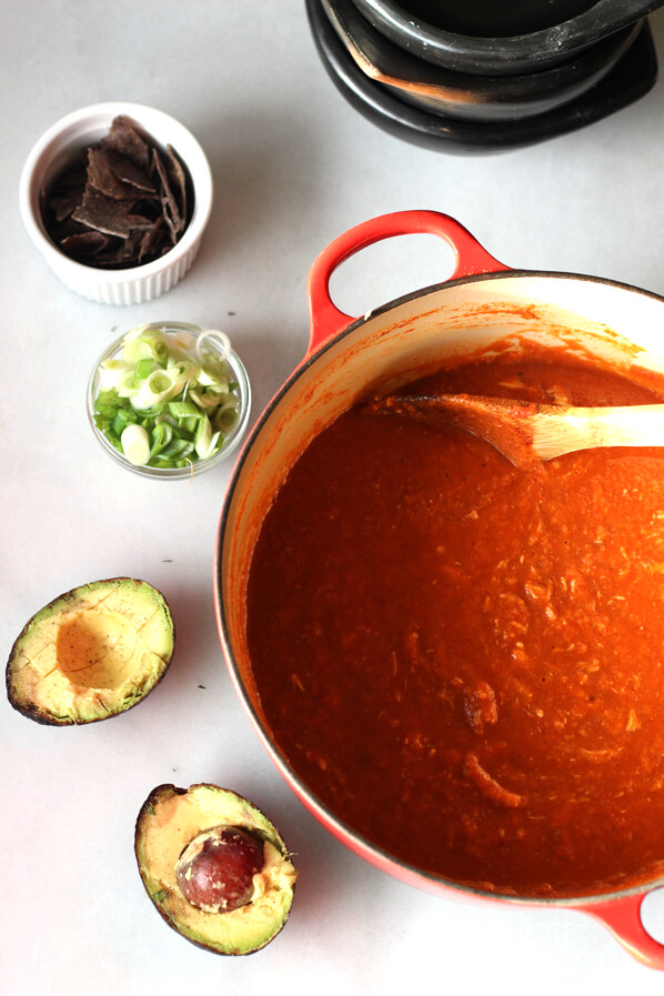 Easy Chicken Tortilla soup blended into dutch oven with additional toppings along side.