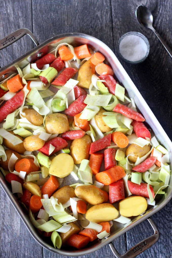 Roasting pan with raw vegetables and a small bowl of salt