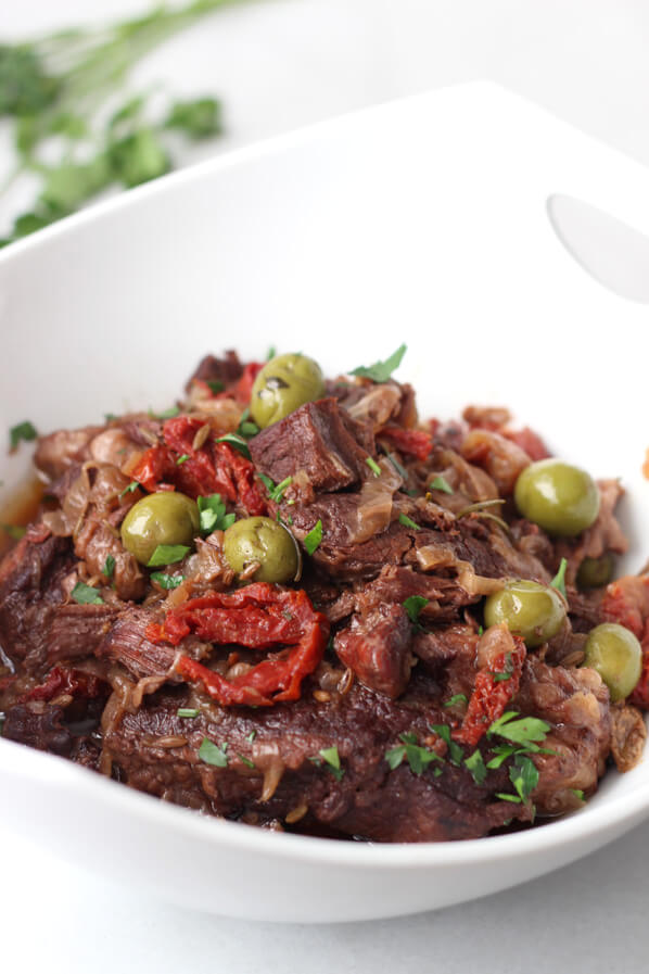 Close up on sun-dried tomato and olive chuck roast in white serving bowl