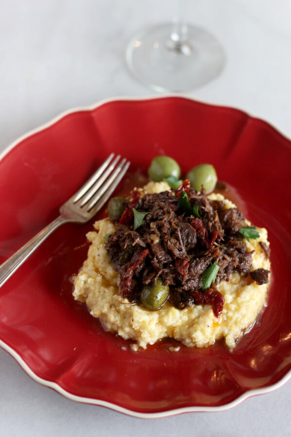 Sun-dried tomato and olive chuck roast on a bed of buttery polenta