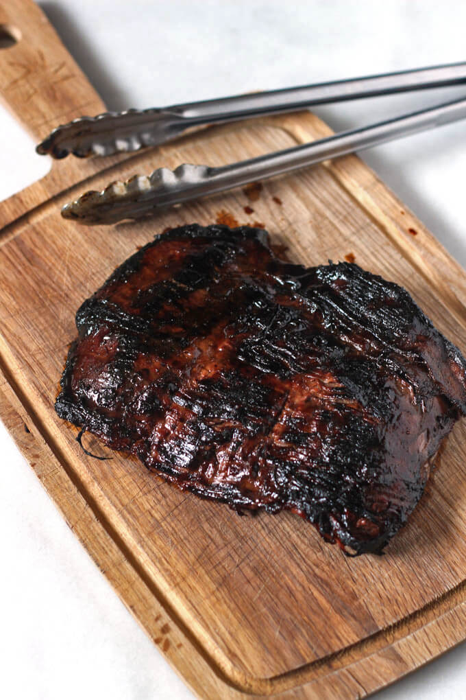 Grilled flank steak on wooden cutting board that has been removed from grill