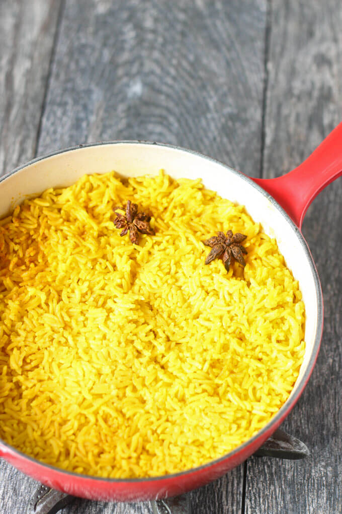 cooked rice in red saute pan with two star anise on top of rice