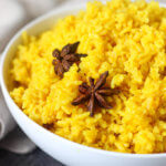 Cooked golden spiced turmeric rice in while bowl with two star anise on top