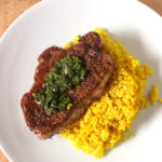 Spiced Pork Chop on bed of yellow rice topped with cilantro parsley chimichurri