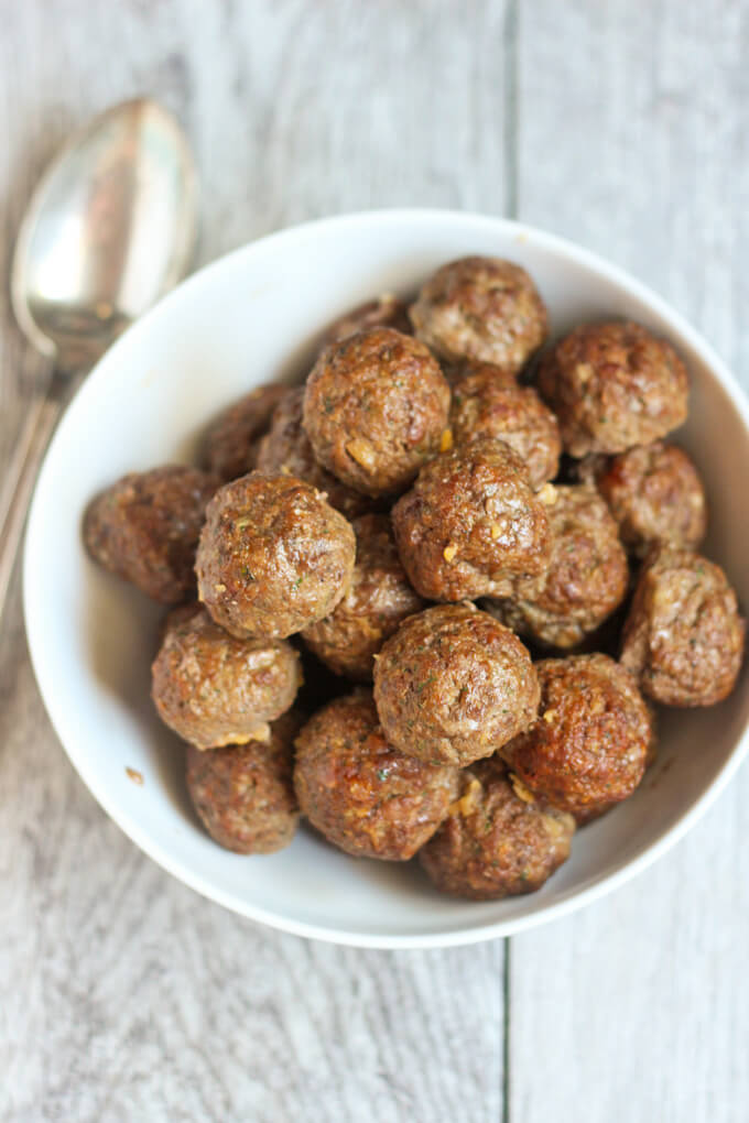 Chili Spiced Meatballs in white bowl with silver spoon on a gray wood textured surface