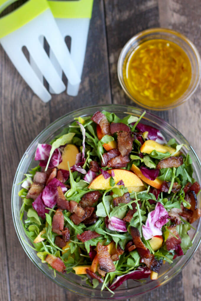 Nectarine, Radicchio, and Arugula salad in bowl with citrus vinaigrette in small bowl and salad tongs