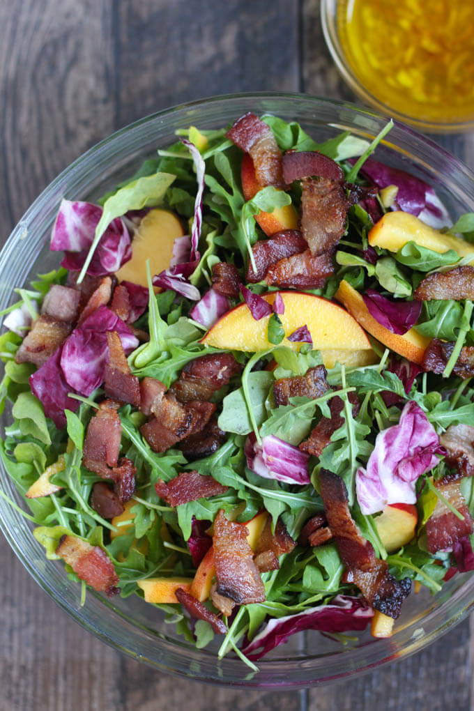 Close up picture of Nectarine, Radicchio and Arugula Salad in glass bowl with citrus vinaigrette in background