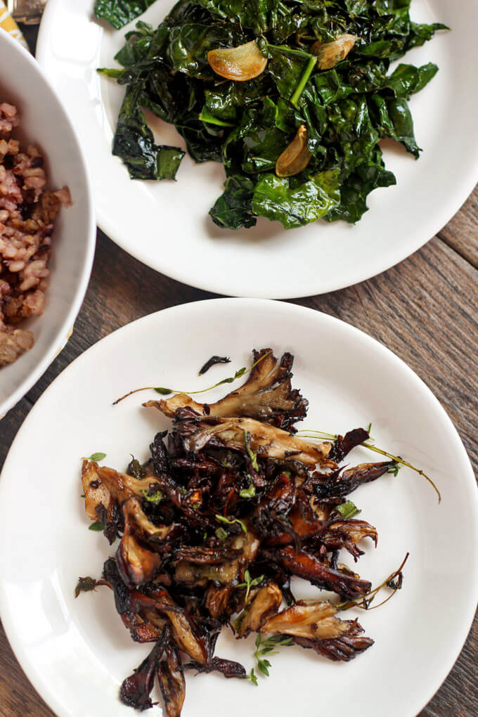 Close up on cooked mushrooms and garlic kale on white plates
