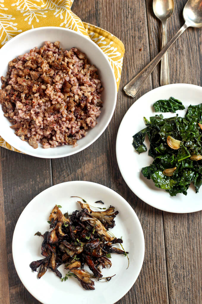 Kale, Mushroom, and Sausage Wild Rice Bow ingredients in white bowl and white plates on wooden surface