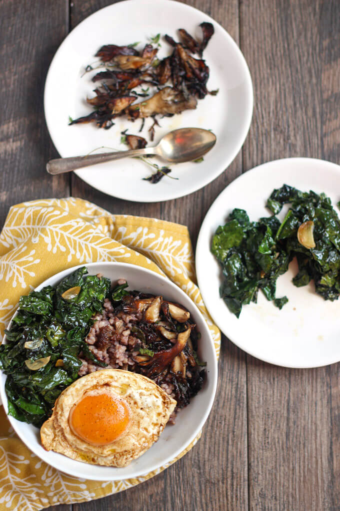 Kale, Mushroom, and Sausage Wild Rice bowl assembled in white bowl with remaining kale on another white plate and mushrooms on a second white plate. All on wooden surface.