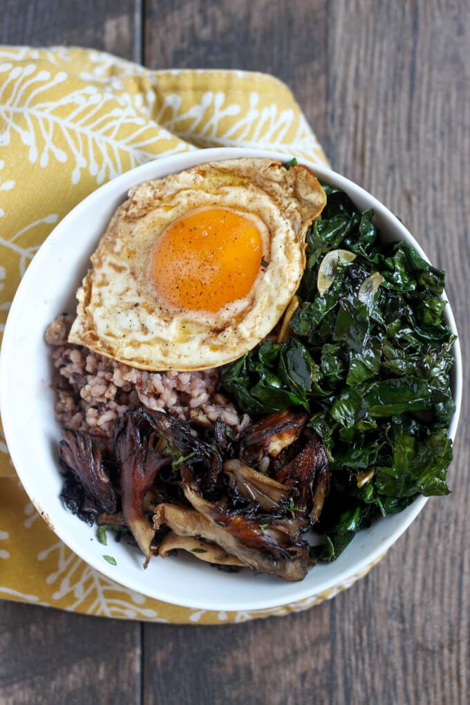 Kale, Mushroom, and Sausage Wild Rice Bowl in white bowl on yellow patterned cloth