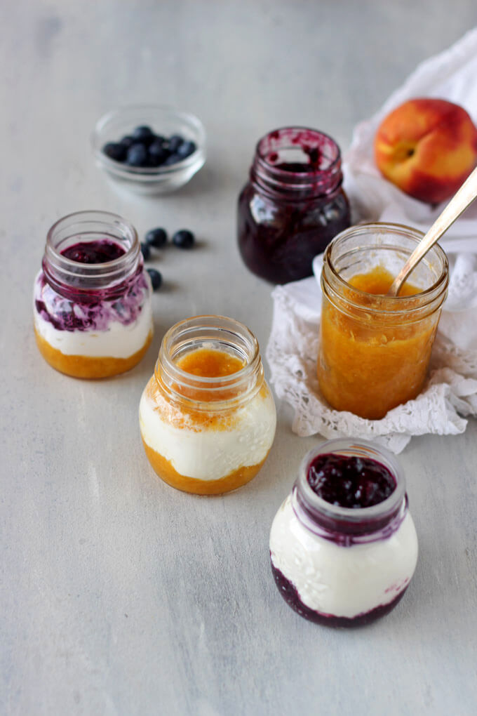 three glass jars with greek yogurt parfaits, a jar of peach jam and jar of blueberry jam with peach and fresh blueberries in background