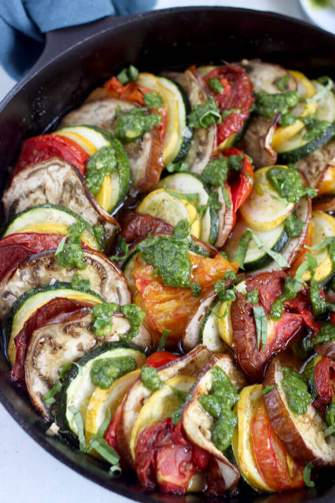 Close up on Roasted Heirloom tomato, zucchini, and eggplant topped with pesto and chopped basil