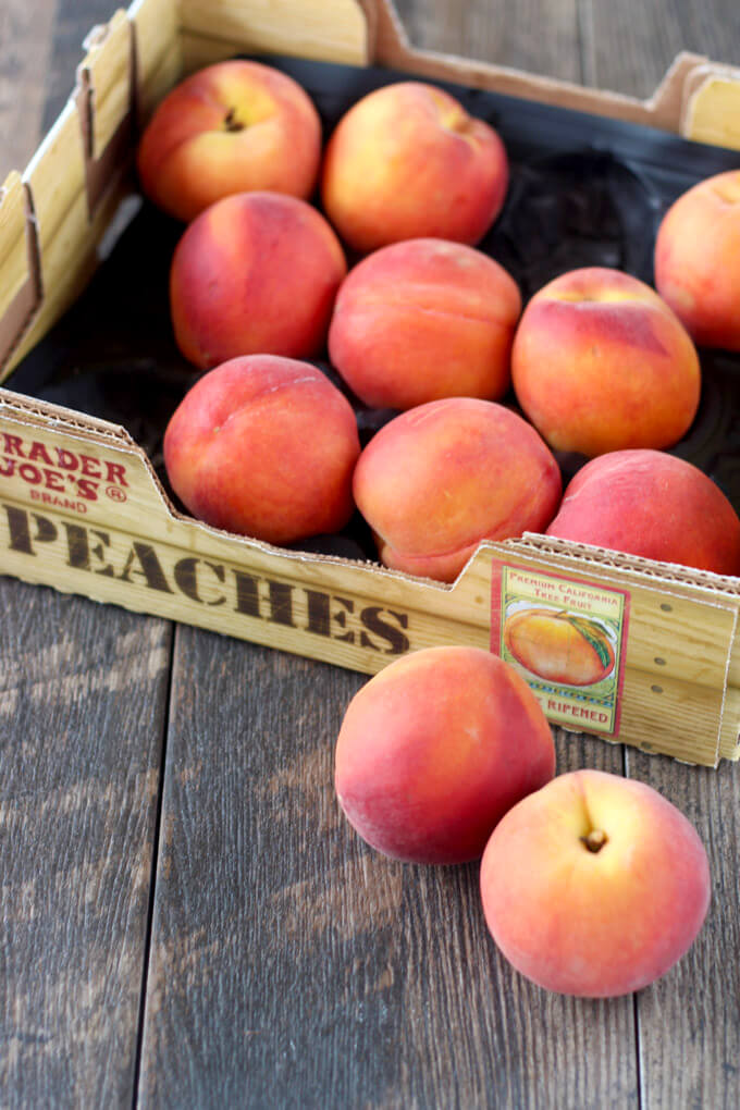 Box of peaches on wooden surface