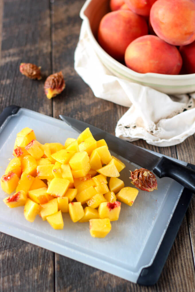 Chopped peaches on cutting boeard with bowl of whole peaches in background