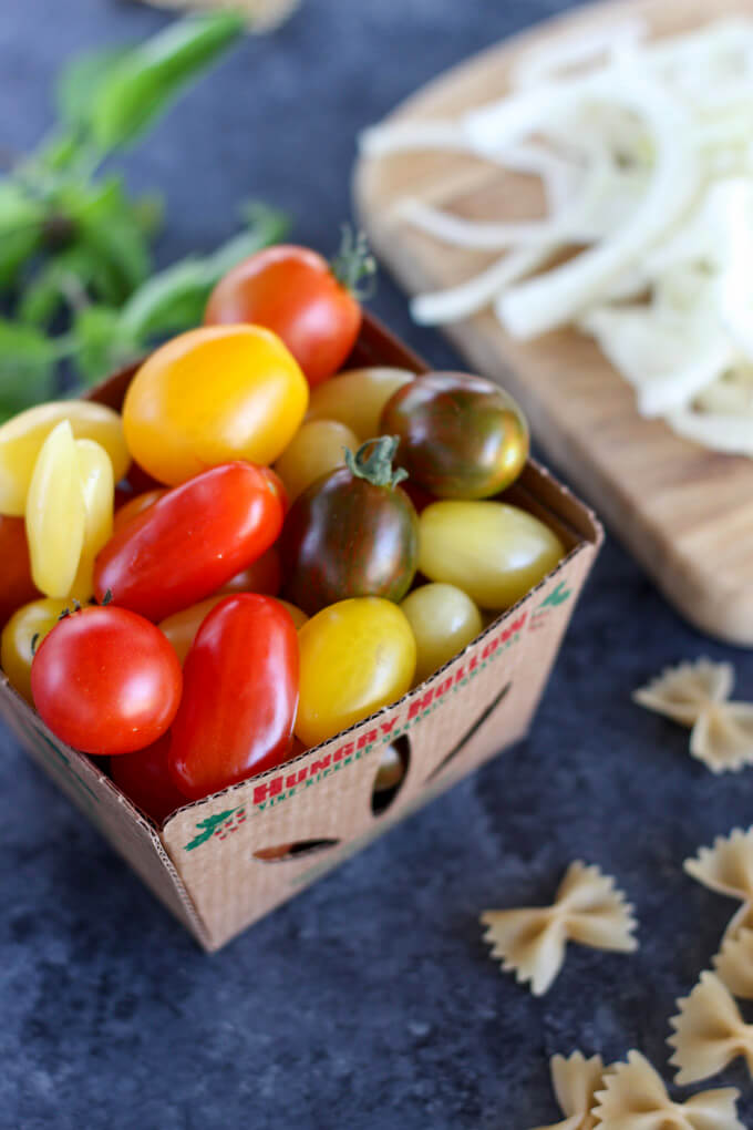 Mixed cherry tomatoes in cardboard box with sliced fennel and basil in background. Dried pasta on surface as well