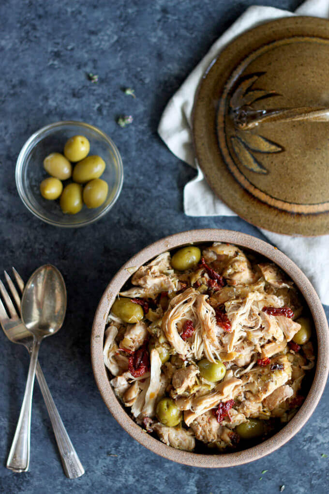 Instant Pot Leek and Olive Chicken in brown cermic bowl with serving spoon and fork beside the bowl and small glass of green olives in background.