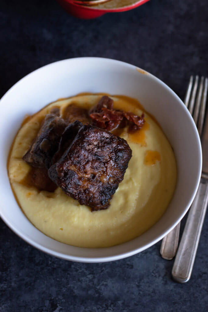White bowl with dijon balsamic short rib on bed of whipped potatoes. Edge of fork and knife on right side of bowl.