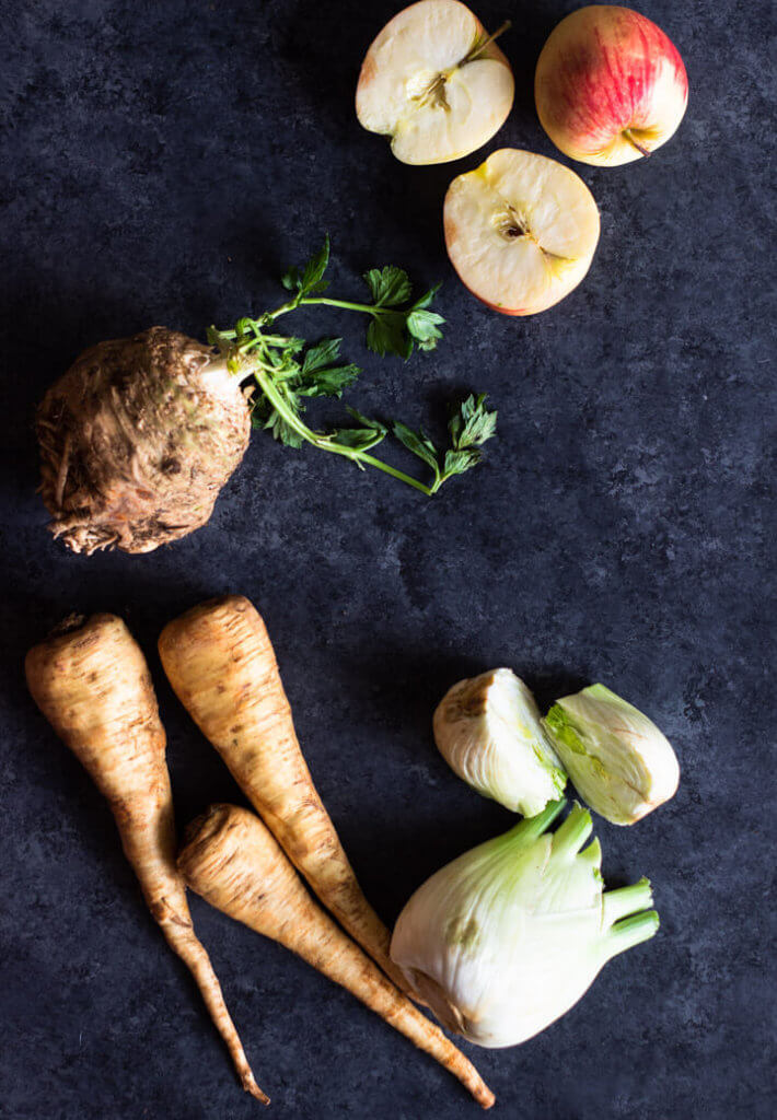 Ingredients for Celeriac, Parsnip, and Fennel Soup laid out on black surface.