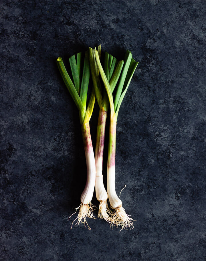 Three green garlic on dark surface