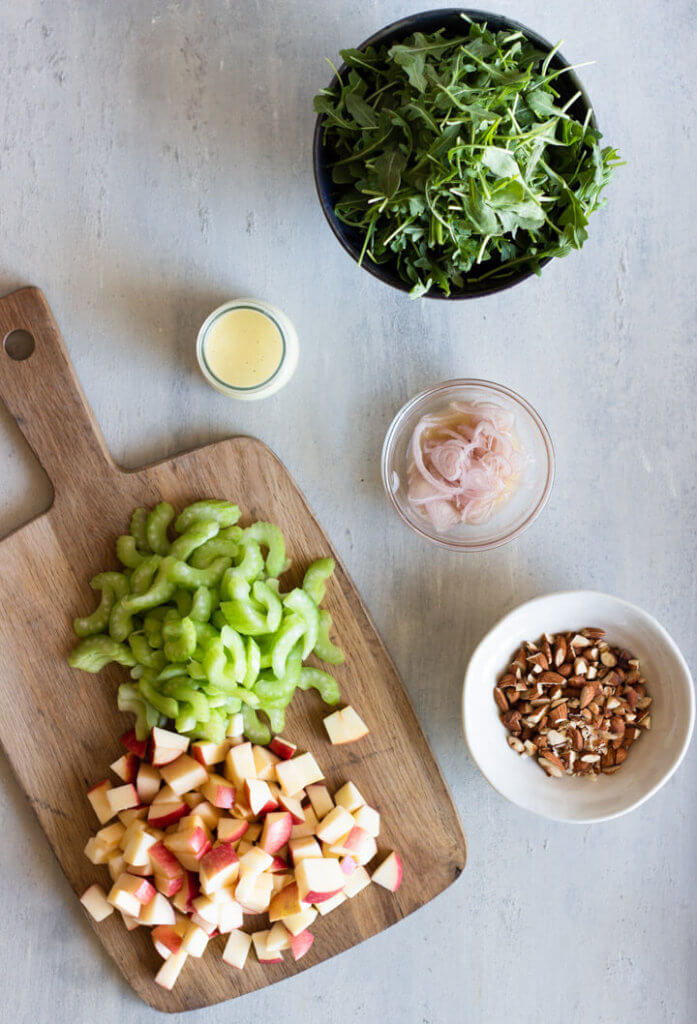 Stone surface with ingredients for Celery, Apple, and Almond salad spread out in various bowls and wooden cutting board.