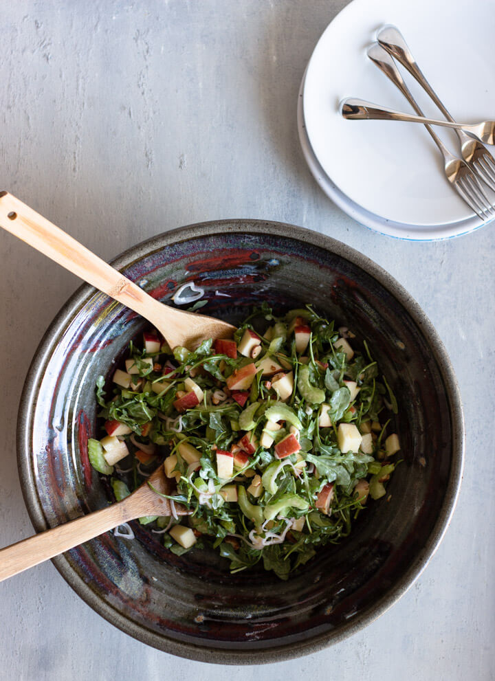 Rustic ceramic bowl filled with celery, apple, and almond salad with two wooden spoons resting inside. Stack of white plates in upper right wih three forks